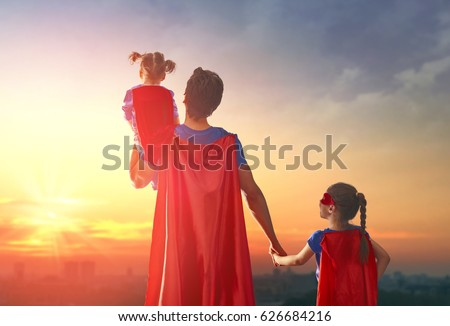 Happy loving family. Dad and his daughters are playing outdoors. Daddy and his children girls in an Superhero's costumes. Concept of Father's day.