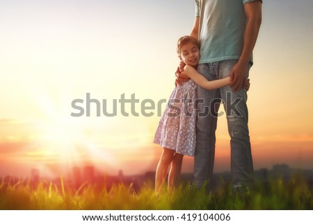Happy loving family. Father and his daughter child girl playing and hugging outdoors. Cute little girl hugs daddy. Concept of Father's day. - stock photo