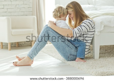 Happy loving family. Mother and child play, kisses and hugs - stock photo