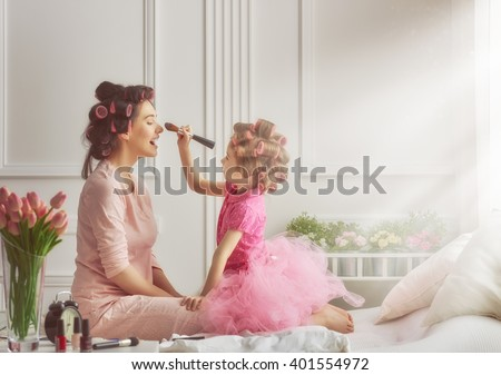 Happy loving family. Mother and daughter are doing hair and having fun. Mother and daughter doing your makeup sitting on the bed in the bedroom. - stock photo