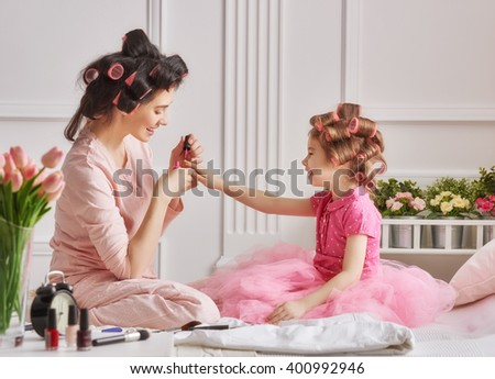 Happy loving family. Mother and daughter are doing hair, manicures and having fun. Mother and daughter sitting on the bed in the bedroom. - stock photo