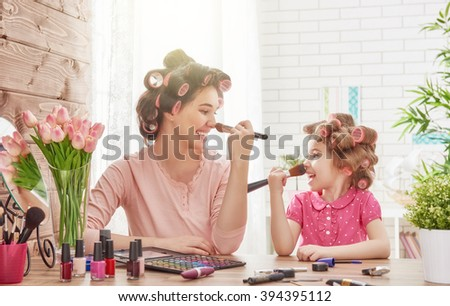 Happy loving family. Mother and daughter are doing hair, manicures, doing your makeup and having fun. Mother and daughter sitting at dressing table at house. - stock photo