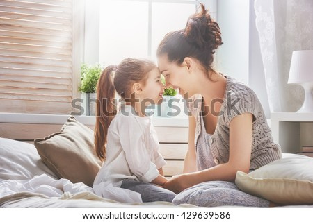 Happy loving family. Mother and her daughter child girl playing in bed. - stock photo