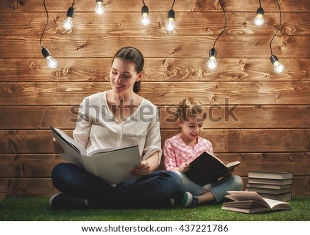 Happy loving family! Pretty young mother reading a book to her daughter - stock photo