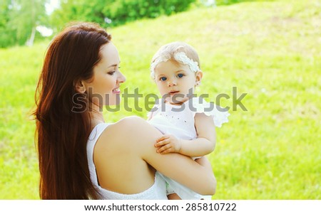 Happy loving mother and baby together outdoors in sunny summer day - stock photo