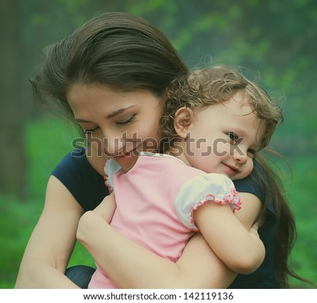 Happy loving mother and girl cuddling outdoor summer background. Closeup tender and love portrait - stock photo