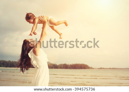 Happy loving mother and her baby child playing outdoors on the sea beach - stock photo