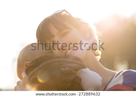 Happy loving protective mother cuddling her young infant to her shoulder with maternal smile backlit by a bright sunburst. - stock photo