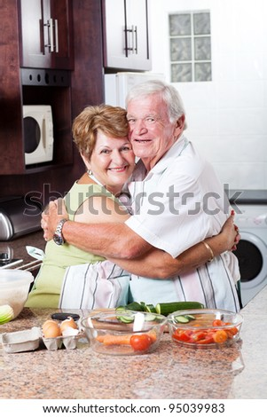 happy loving senior couple hugging in kitchen - stock photo