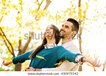 Happy loving young couple at the park - stock photo