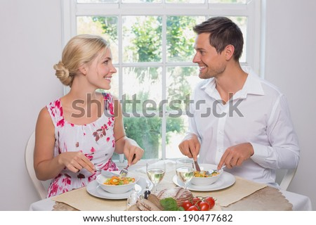 Happy loving young couple looking at each other while having food at home - stock photo