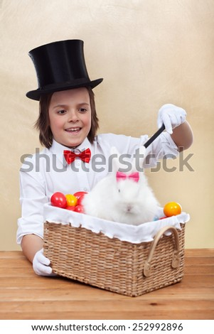 Happy magician boy conjuring an easter rabbit and colorful eggs into a basket- shallow depth of field - stock photo