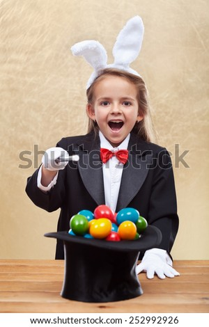 Happy magician girl with bunny ears conjuring colorful easter eggs- shallow depth of field