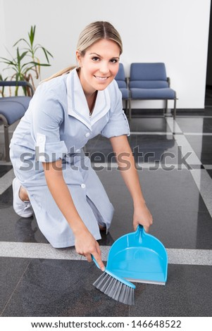 Happy Maid Sweeping The Floor With Duster And Dust Tray - stock photo