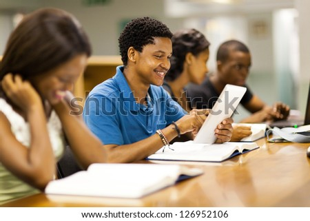 happy male african american college student using tablet computer - stock photo