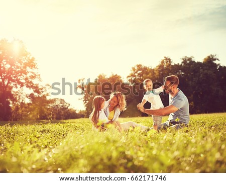 Happy male and female playing with children outside