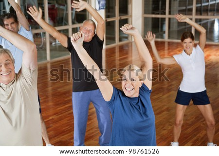 Happy male and female seniors dancing to music in gym - stock photo