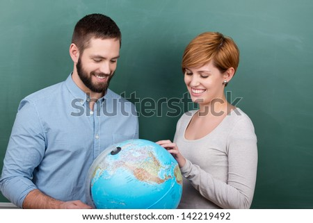 Happy male and female teachers examining globe together against chalkboard - stock photo