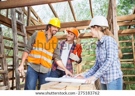 Happy male and female workers discussing over blueprint in incomplete wooden cabin at site - stock photo