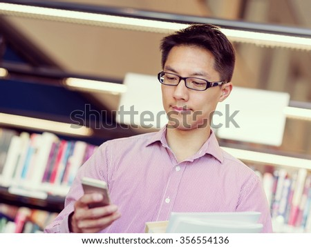Happy male asian student holding books and his mobile at the library
