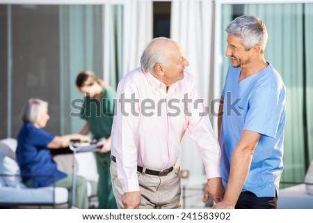 Happy male caretaker looking at disabled senior man at nursing home yard - stock photo
