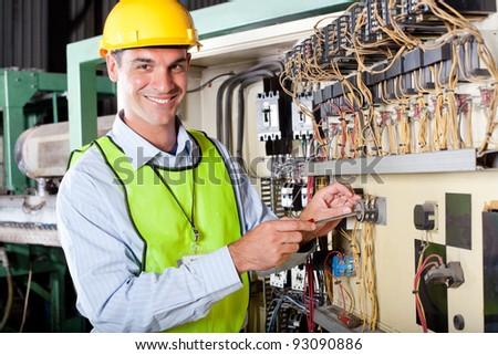 happy male caucasian technician repairing industrial machine control box