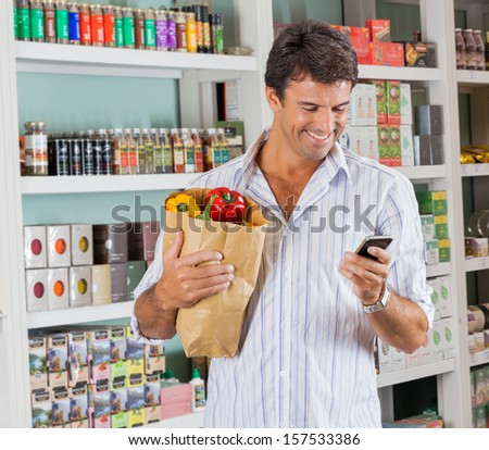 Happy male customer with grocery paper bag using mobile phone in supermarket - stock photo