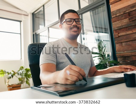 Happy male designer in office working with digital graphic tablet and digital pen.  Creative sitting at desk and looking in camera smiling. - stock photo