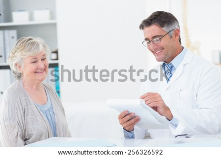 Happy male doctor writing prescriptions for senior patient in clinic - stock photo