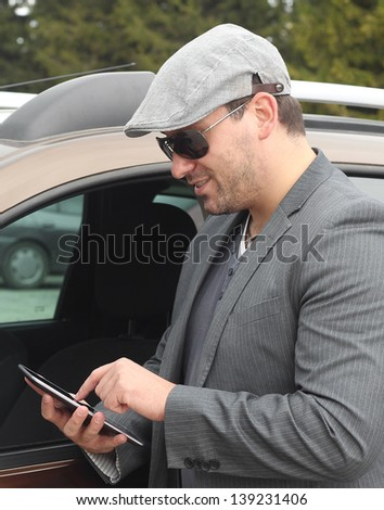 Happy male driver smiling while standing by a car with open front window and checking using internet via tablet. Selective focus. - stock photo
