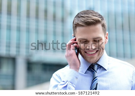 Happy male executive on call outside office building - stock photo