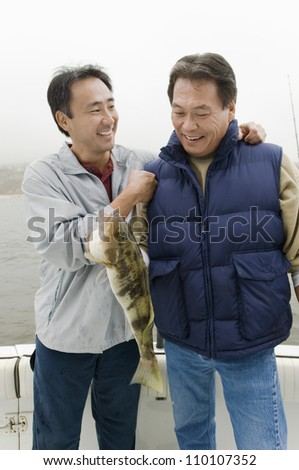 Happy male friends with a catch on a fishing boat - stock photo