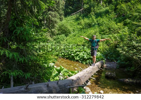 Happy male hiker crossing a mountain river on a huge tree trunk - stock photo