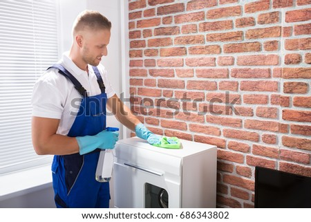 Happy Male Janitor In Uniform Cleaning The Furniture With Rag And Spray