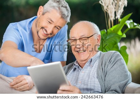 Happy male nurse and senior man enjoying while using tablet computer in nursing home porch - stock photo