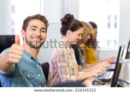 Happy male student gesturing thumbs up in computer class - stock photo