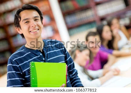 Happy male student smiling with a group at the background - stock photo