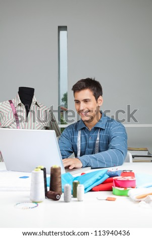 Happy male tailor using laptop while sitting by table with dressmaking accessories