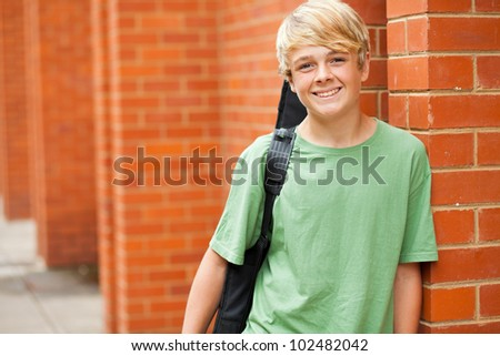 happy male teen musician carrying his guitar - stock photo