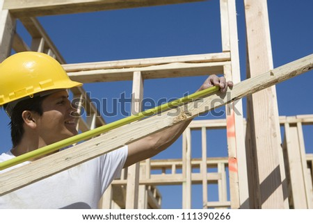 Happy male worker measuring lumber with measure tape at construction site - stock photo