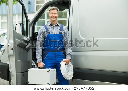 Happy Male Worker With Wire And Toolbox In Front Of Van - stock photo