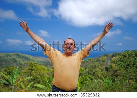 Happy man against the sky, ocean and jungle. - stock photo