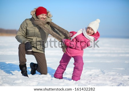 Happy man and his daughter having fun outside in winter
