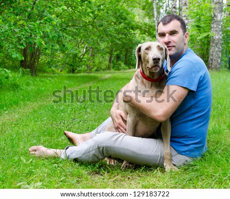 Happy man and his dog outdoors - stock photo