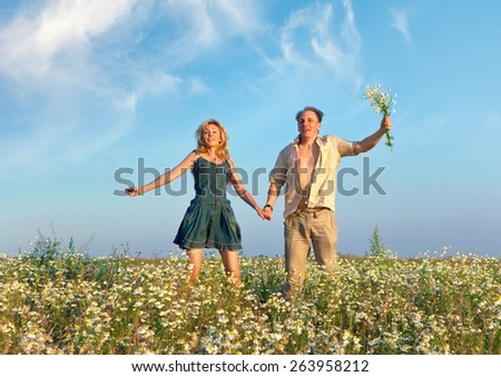 Happy man and the woman jump in the field with camomiles - stock photo