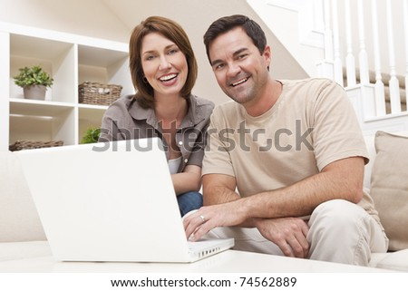 Happy man and woman couple in their thirties, sitting together at home on a sofa using a laptop computer