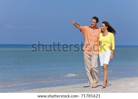 Happy man and woman couple walking and pointing on a deserted beach with bright clear blue sky - stock photo