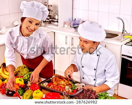 Happy man and woman in chef hat cooking chicken. - stock photo