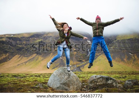happy man and woman jumping by mountains