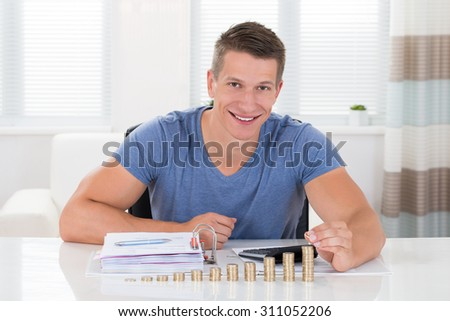 Happy Man Calculating Invoice With Coins At Desk In Living Room